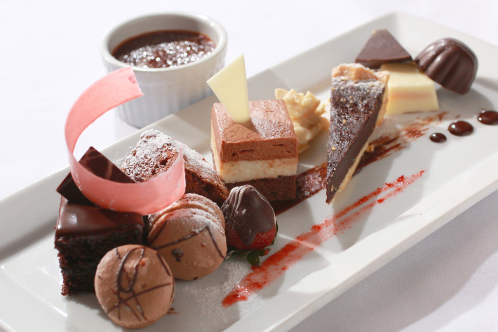 a selection of assorted pralines, chocolate-strawberries, chocolate tart, duo of chocolate mousse, chocolate creme brûlée, chocolate macarons, decadent chocolate cake and fudge brownies